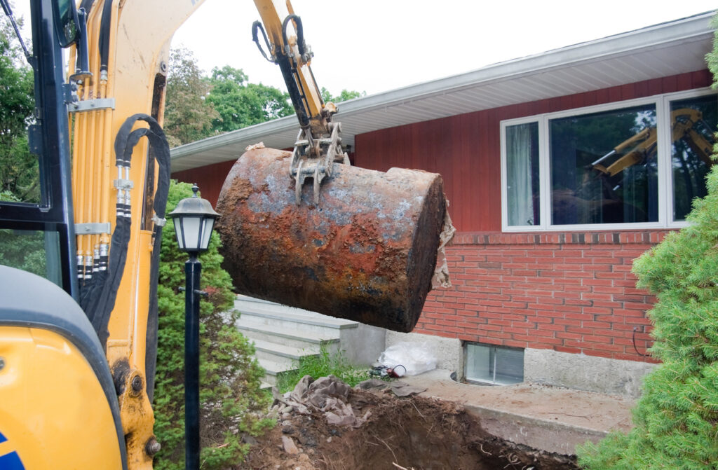 old rusted oil tank being removed from ground
